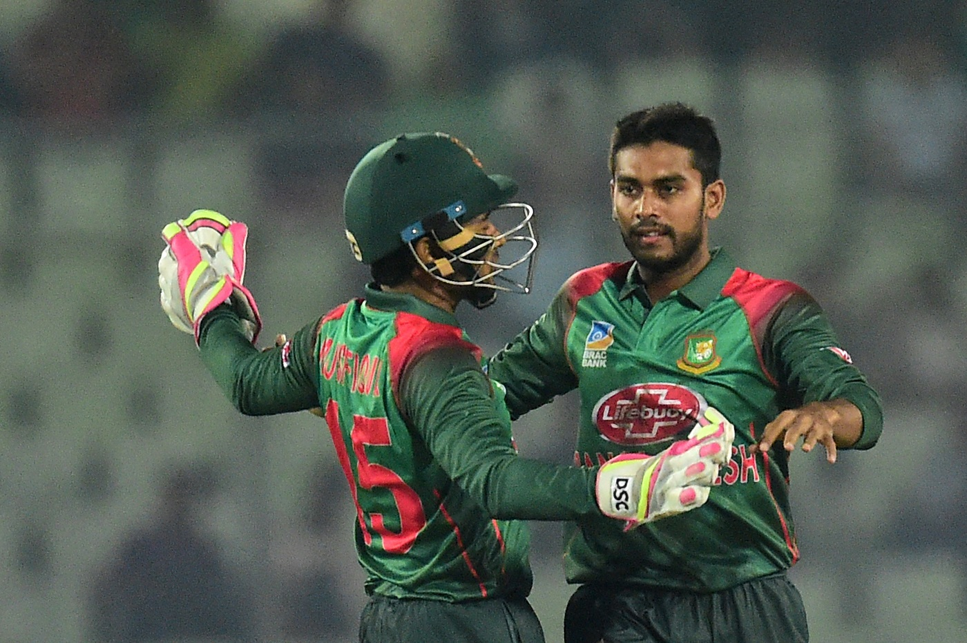 BangladeshI cricketer Mehidy Hasan (R) celebrates with teammate Mushfiqur Rahim (L) (Photo by MUNIR UZ ZAMAN / AFP)